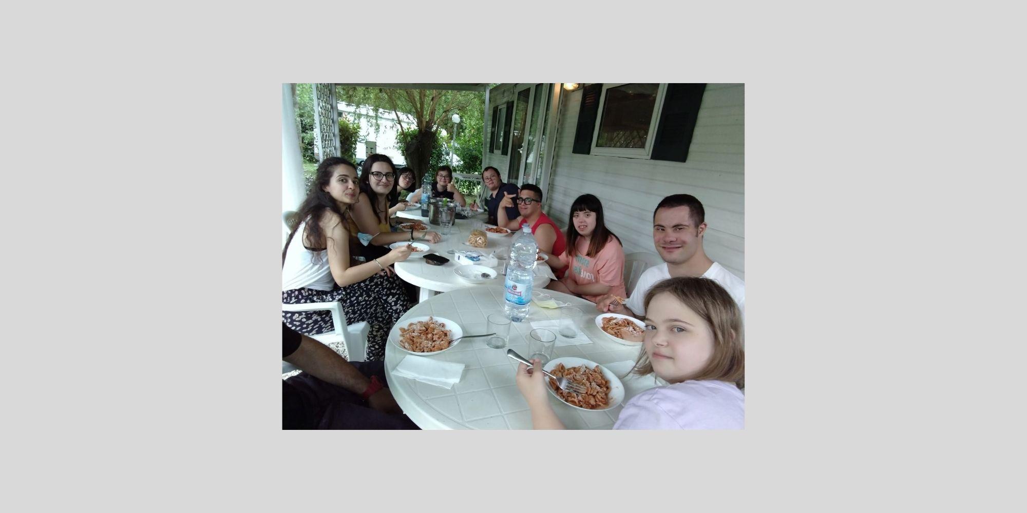 Gruppo giovani con sindrome di Down attorno al tavolo in vacanza