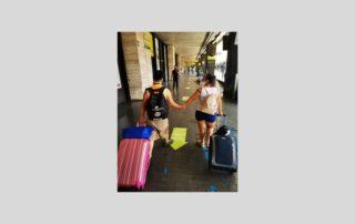 coppia di giovani con sindrome di Down che si tengono per mano alla stazione con le valigie